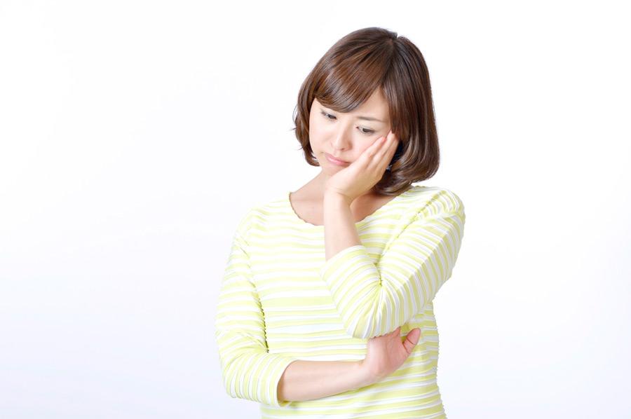 フリー写真 頬に手を当てて悩んでいる日本人女性