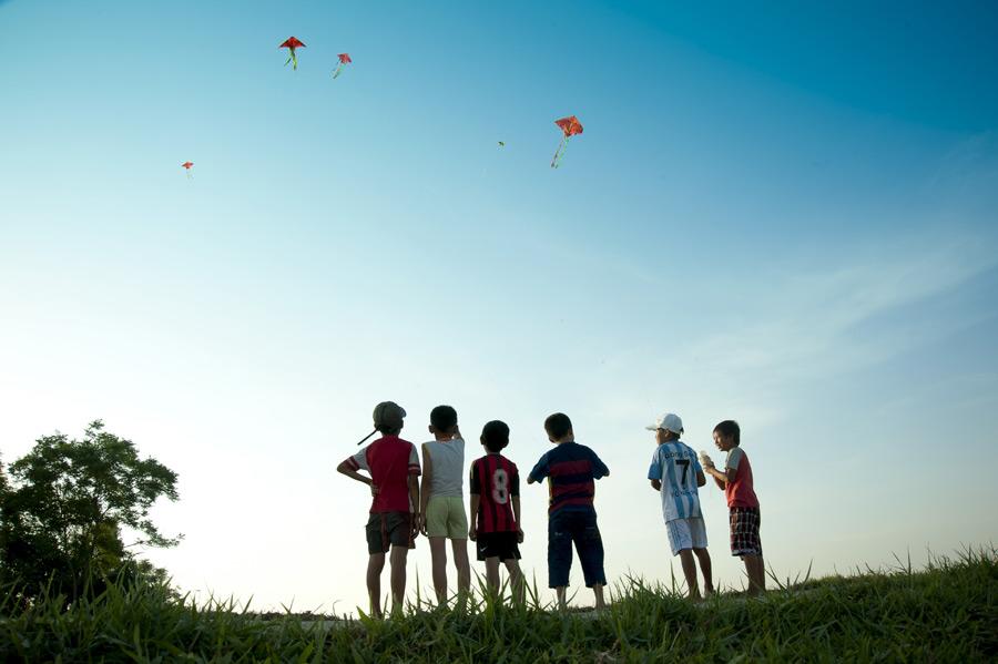フリー写真 凧上げを楽しむ子供たちの後ろ姿