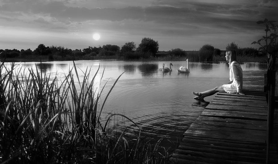 フリー写真 桟橋に座って湖に足をつける少女