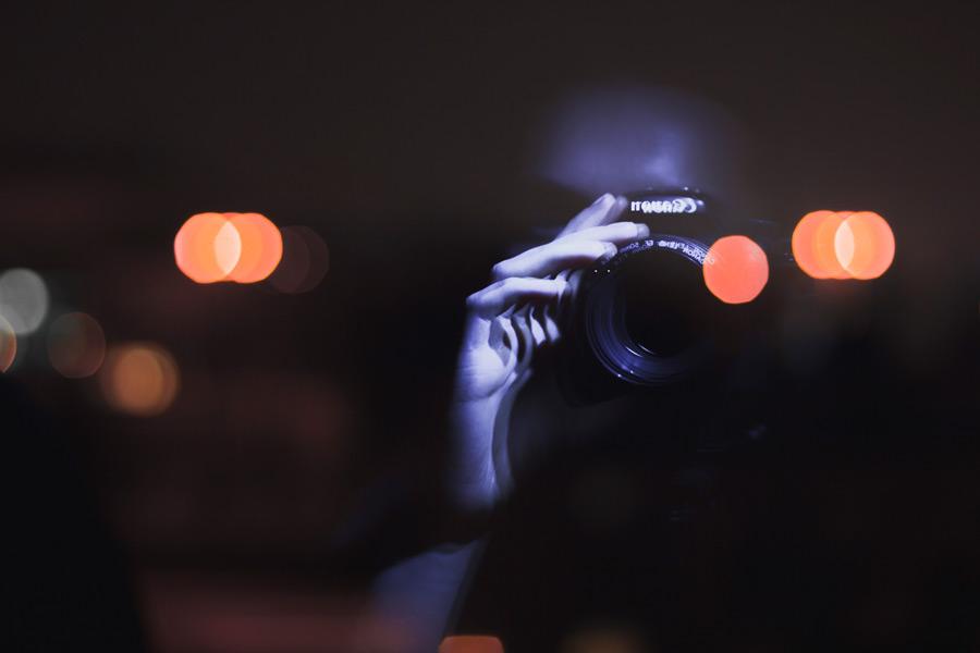 フリー写真 窓に映る一眼レフカメラを構える人物