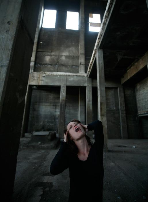 フリー写真 廃墟で頭を抱えて苦しんでいる外国人女性
