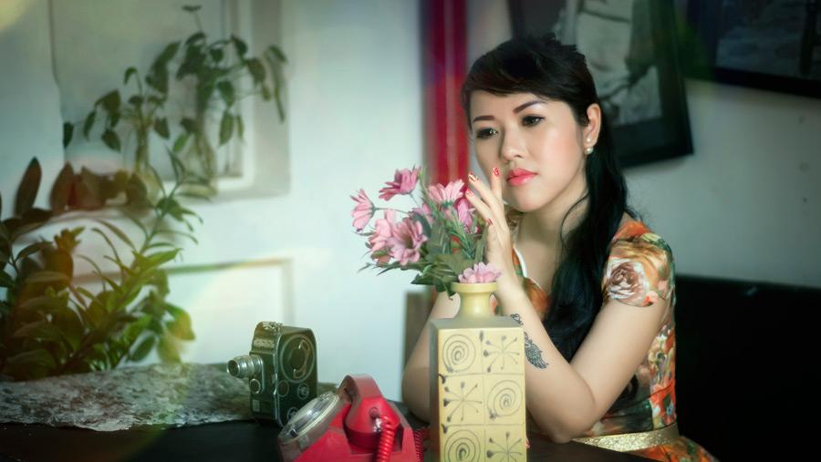 フリー写真 花瓶の花を見つめる女性