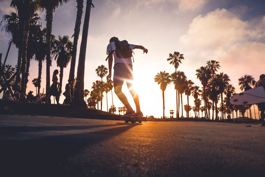 フリー写真 夕日とスケボーに乗る男性