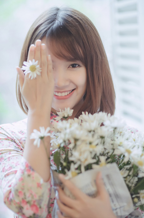 フリー写真 指の隙間に花を挟むベトナム人女性