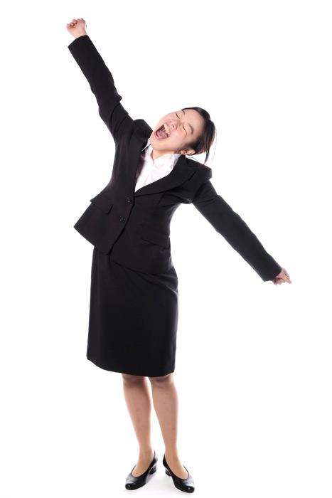 フリー写真 欠伸をしながら背伸びする女性社員