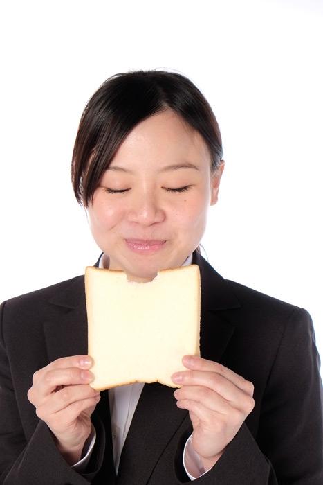 フリー写真 食パンを食べる女性社員