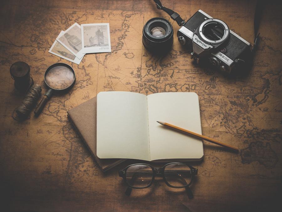 フリー写真 古地図の上の手帳とカメラと眼鏡