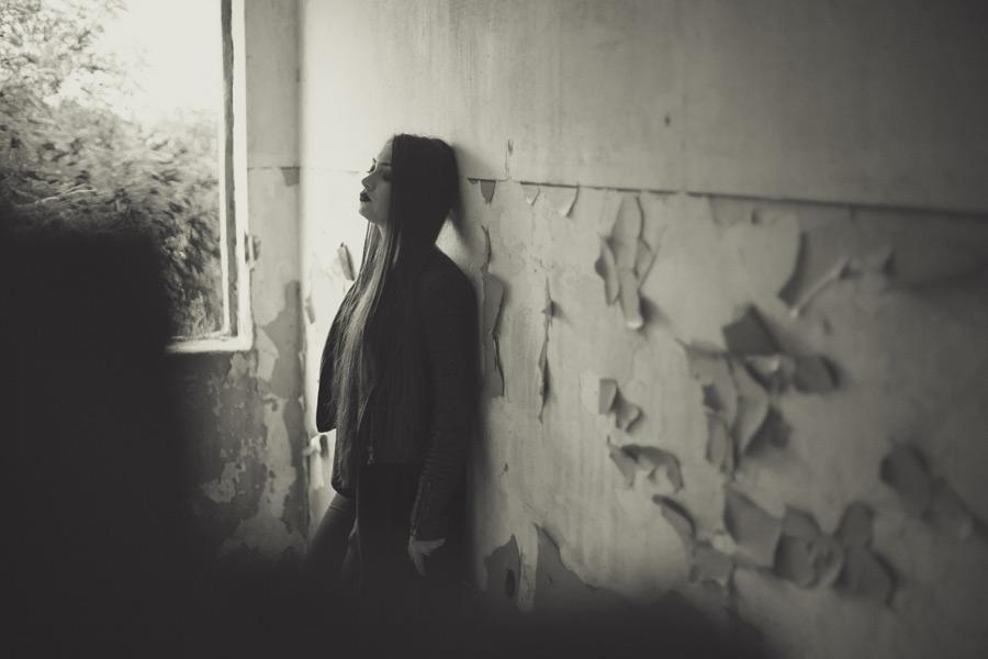 フリー写真 廃墟の壁にもたれかかる外国人女性