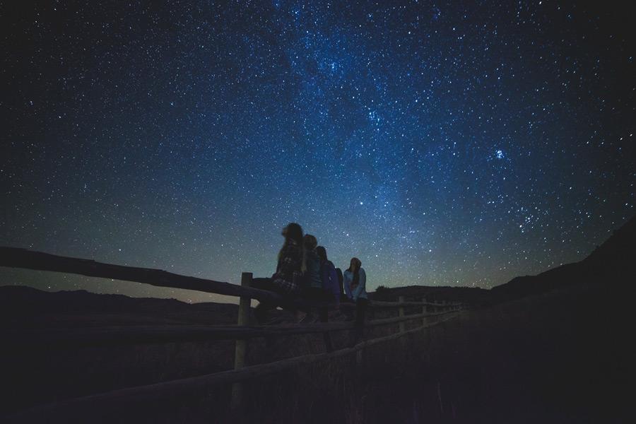 フリー写真 柵に座って星を眺める少女たち