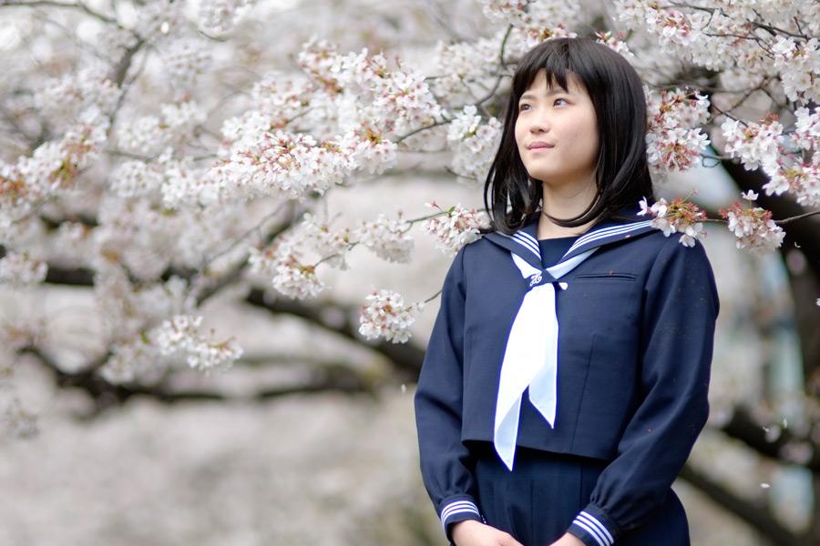 フリー写真 桜の花の前で空を見上げている女子高生