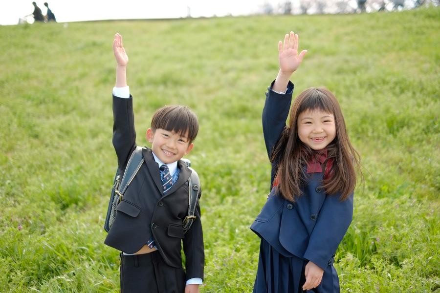 フリー写真 手を上げる小学生の男の子と女の子