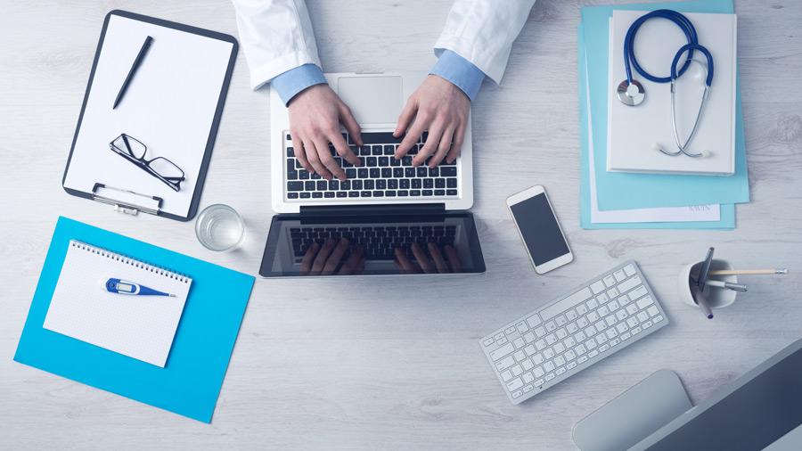 フリー写真 ノートパソコンを利用中の医者の机の上