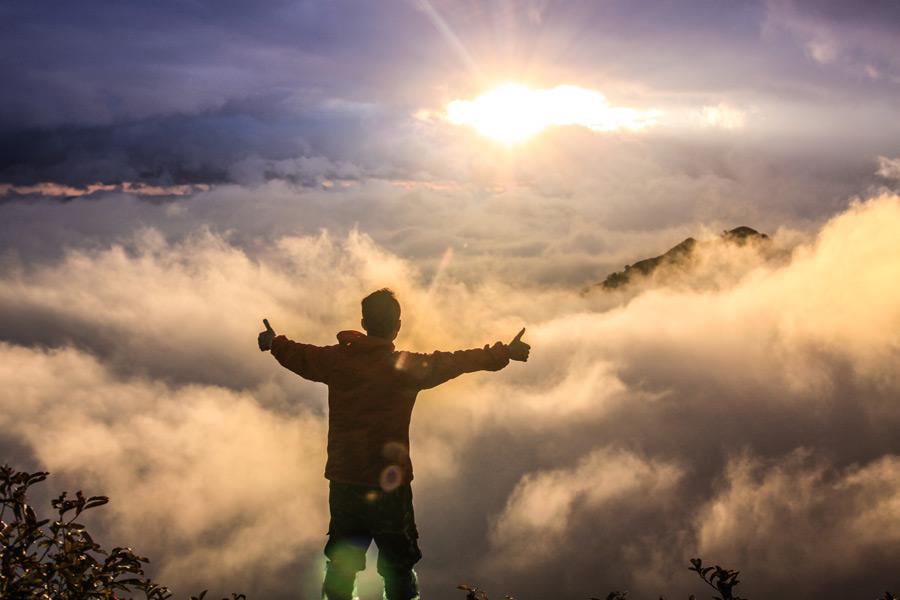 フリー写真 雲海と朝日を眺める男性の後ろ姿