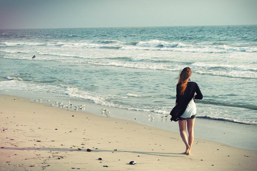 フリー写真 波打ち際を歩く女性とミユビシギの群れ