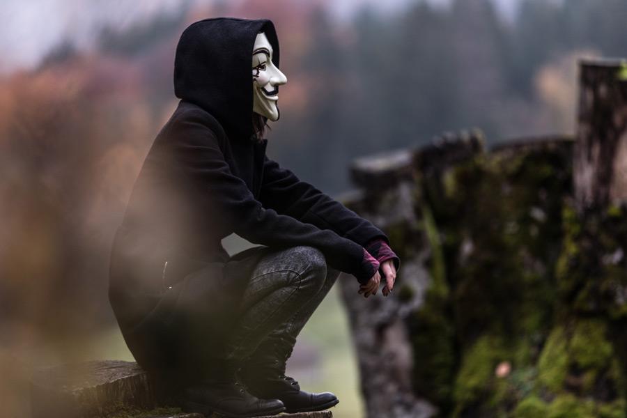 フリー写真 アノニマスの仮面を被って腰掛ける人物