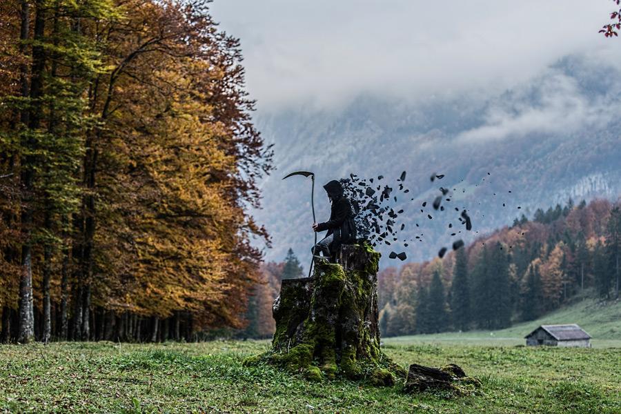 フリー写真 大鎌を持った死神と田舎の風景
