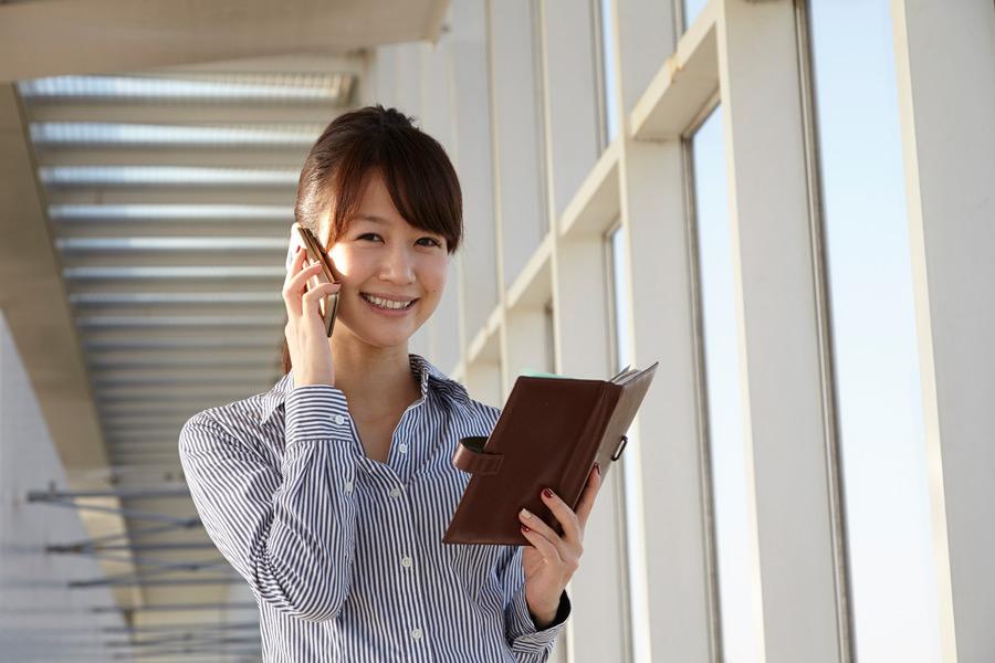 フリー写真 手帳を開けながら携帯電話で話す女性社員