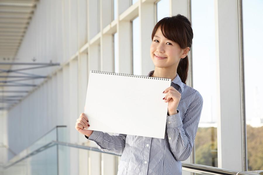 フリー写真 スケッチブックを掲げる日本人の女性社員