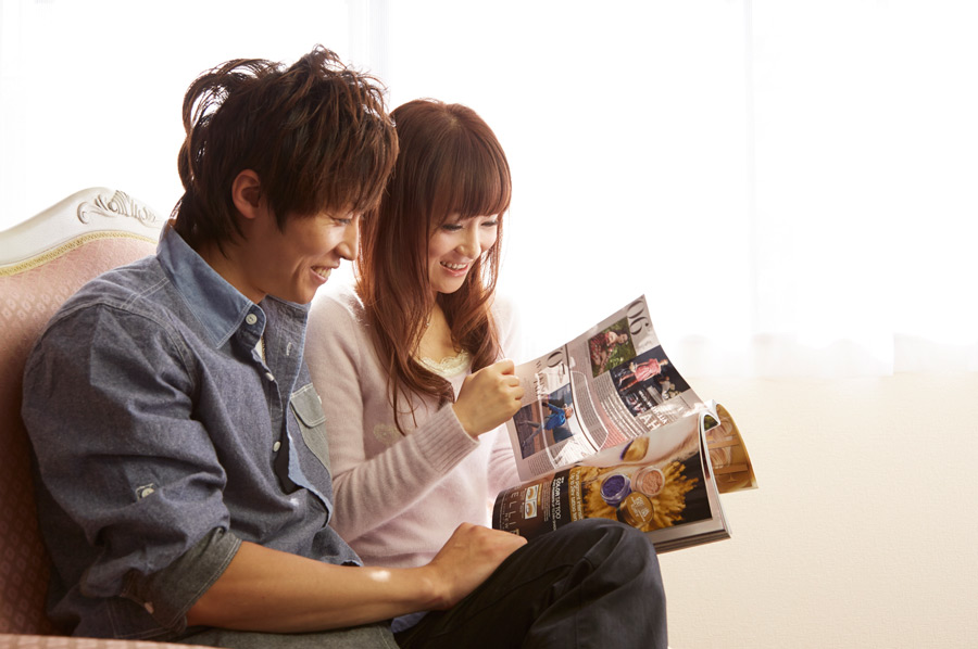 フリー写真 ソファーに座って雑誌を見ているカップル