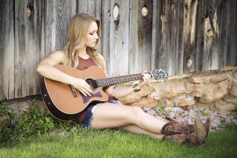 フリー写真 小屋の前に座ってギターを弾く外国人女性