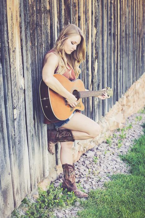 フリー写真 壁にもたれながらギターを弾く外国人女性