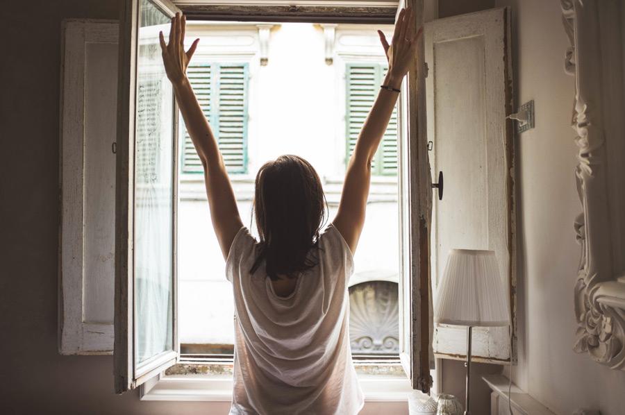 フリー写真 窓を開けて背伸びする女性の後ろ姿
