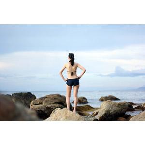 フリー写真, 人物, 女性, 外国人女性, 後ろ姿, 水着, ビキニ, 人と風景, 腰に手を当てる, 岩, 海岸, 海, ポニーテール