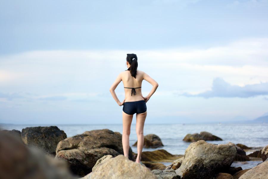 フリー写真 水着姿で海岸に立つ女性の後ろ姿