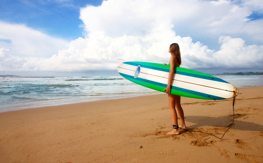 フリー写真 ビーチでサーフボート抱える外国人女性