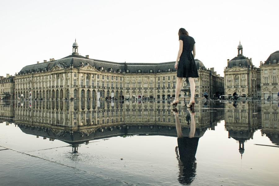 フリー写真 水たまりに映るブルス広場と女性