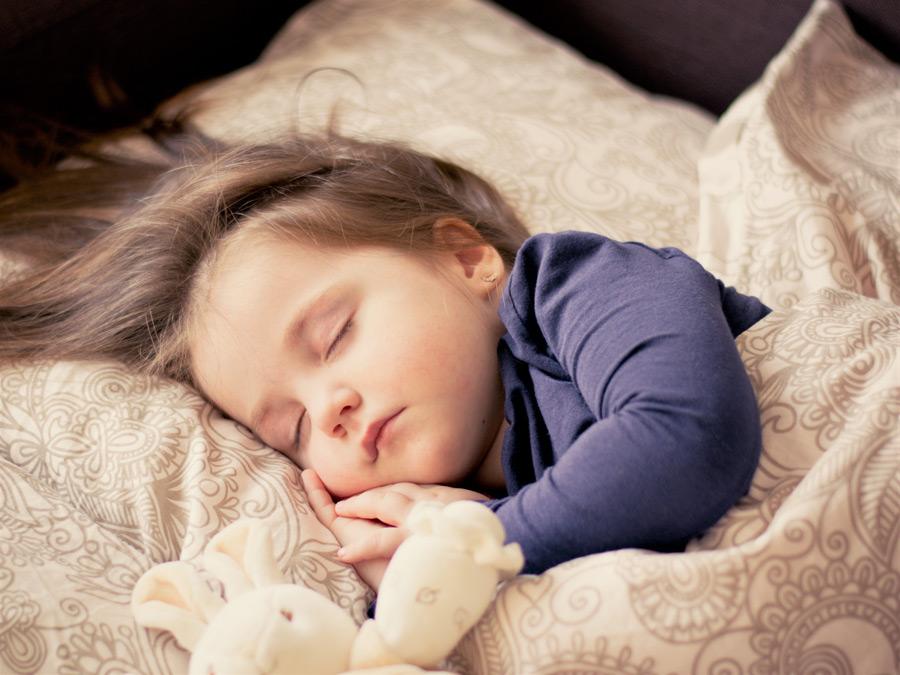 フリー写真 布団に入って眠っている外国の女の子