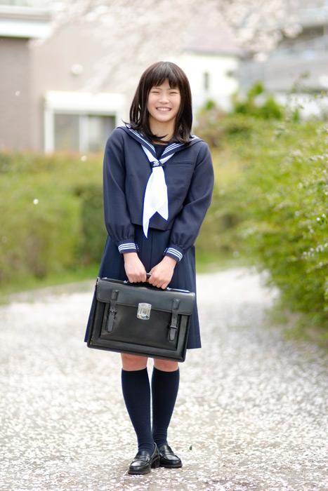 フリー写真 桜と通学かばんを持つ笑顔の女子高生