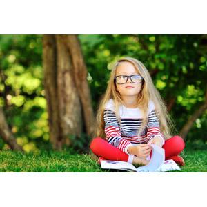 フリー写真, 人物, 子供, 女の子, 外国の女の子, 眼鏡(メガネ), 座る(地面), あぐらをかく, 本(書籍), 読む(読書)