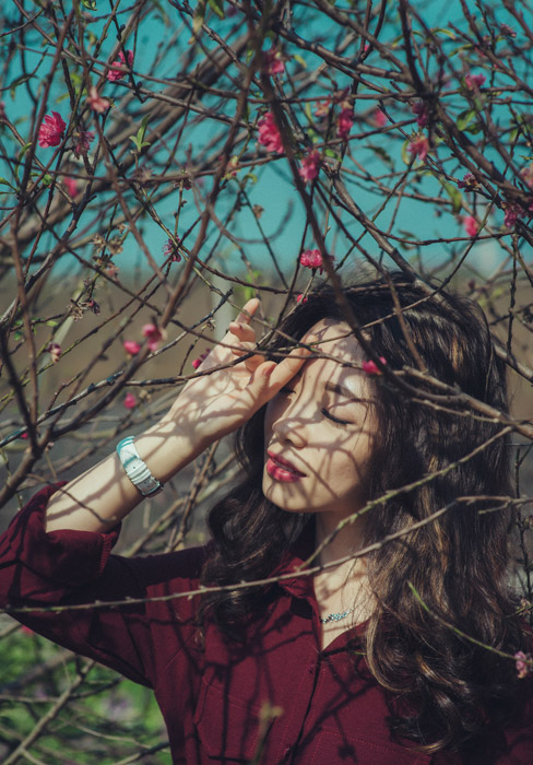 フリー写真 梅の花が咲く枝と目を閉じる女性