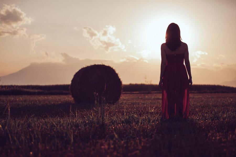 フリー写真 牧草地に立つ女性の後ろ姿