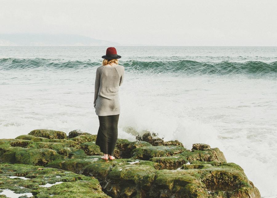 フリー写真 岩の上に立って海を眺める女性の後ろ姿