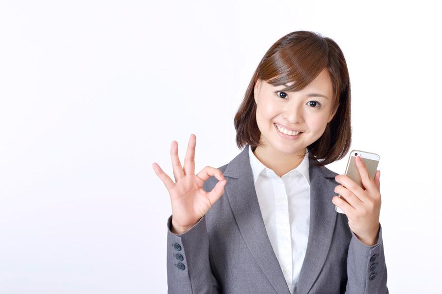 フリー写真 スマホを持ってOKサインの日本の女性社員