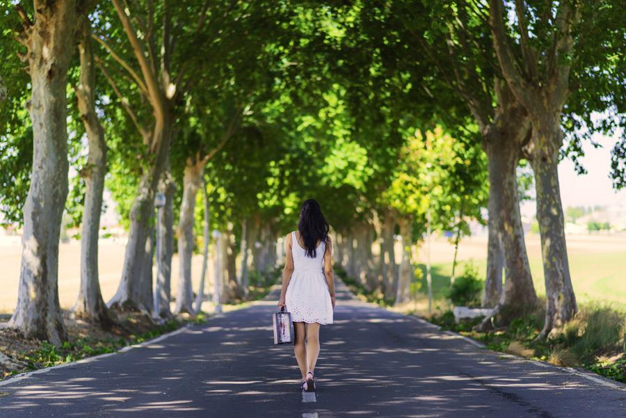 フリー写真 トランクを持って並木道を歩く女性の後ろ姿