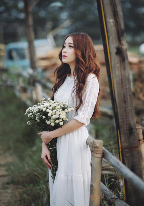 フリー写真 花束を持って遠くを見ている女性