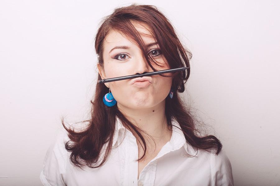 フリー写真 鼻と口の間に鉛筆をはさむ外国人女性