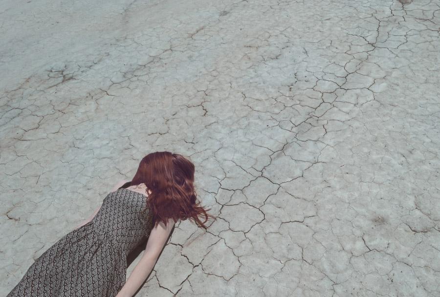 フリー写真 地割れと髪の毛に顔が隠れている女性