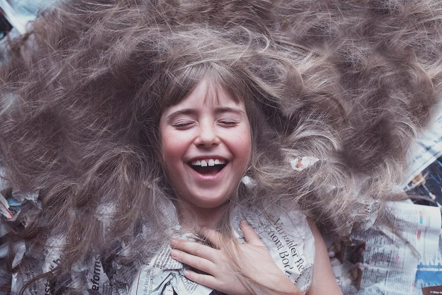 フリー写真 新聞の上で髪の毛を広げる女の子