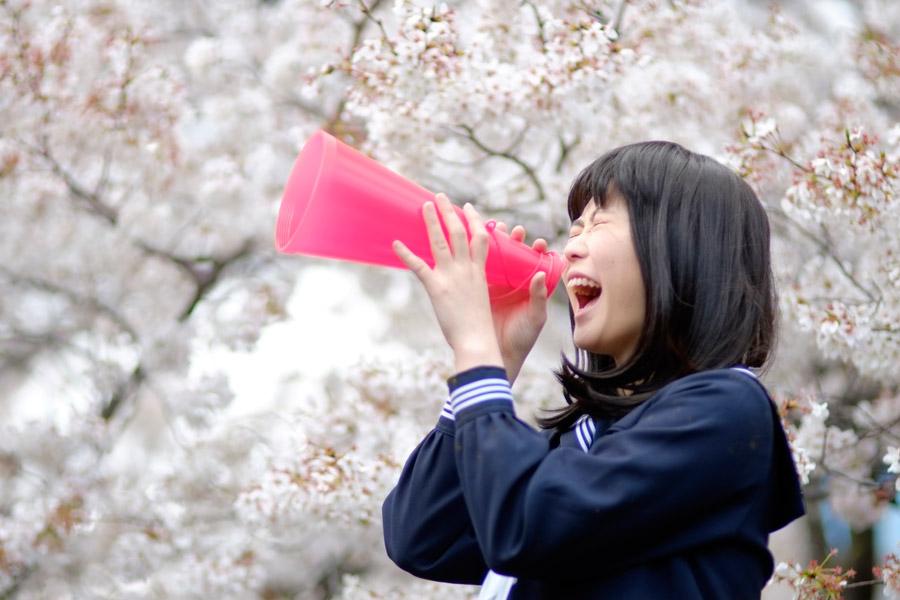 フリー写真 桜の前で声援を送る女子高生