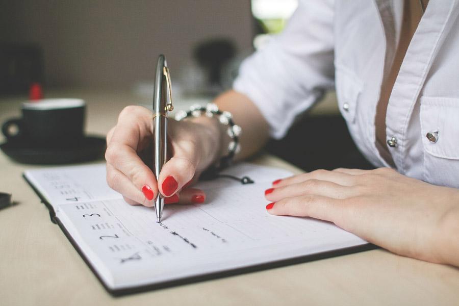 フリー写真 システム手帳に予定を書きこむビジネスウーマン