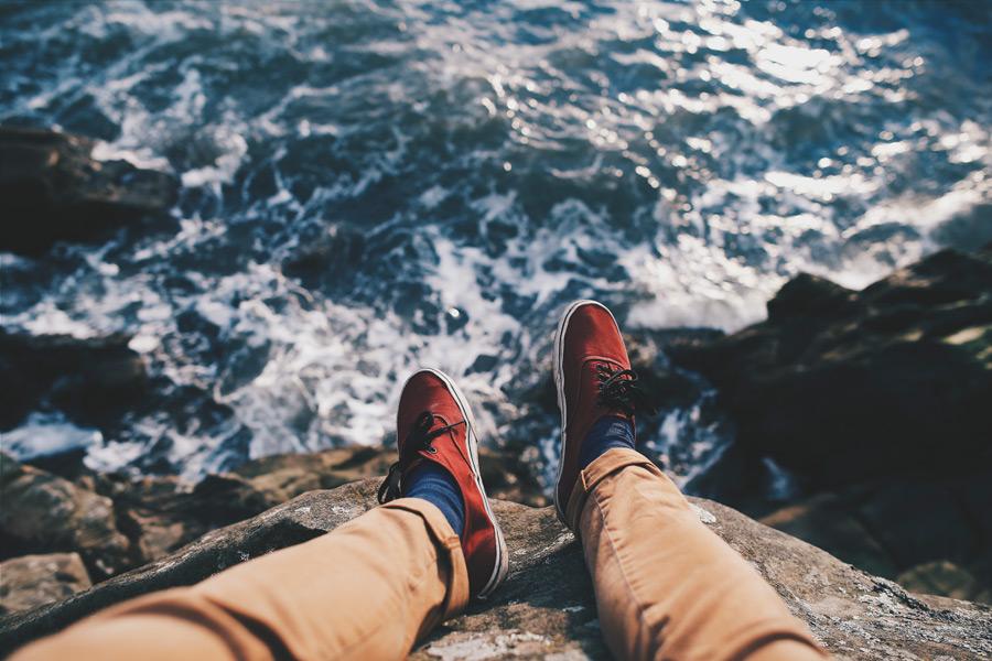フリー写真 崖の上から投げ出した足と海
