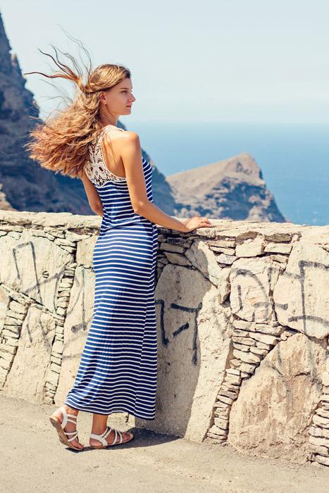フリー写真 風に吹かれながら海を眺める外国人女性