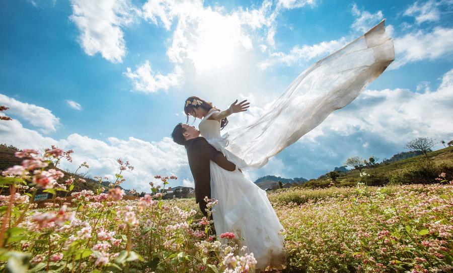 フリー写真 花畑で新婦を抱き上げる新郎
