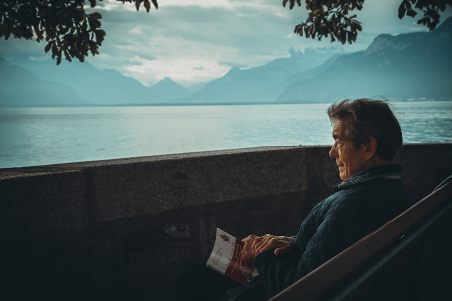 フリー写真 ベンチに座ってルツェルン湖を眺めるシニア男性