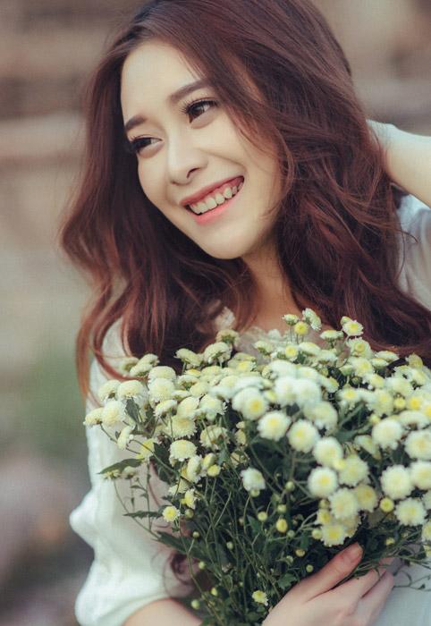 フリー写真 花束を抱えながら笑顔のベトナム人女性