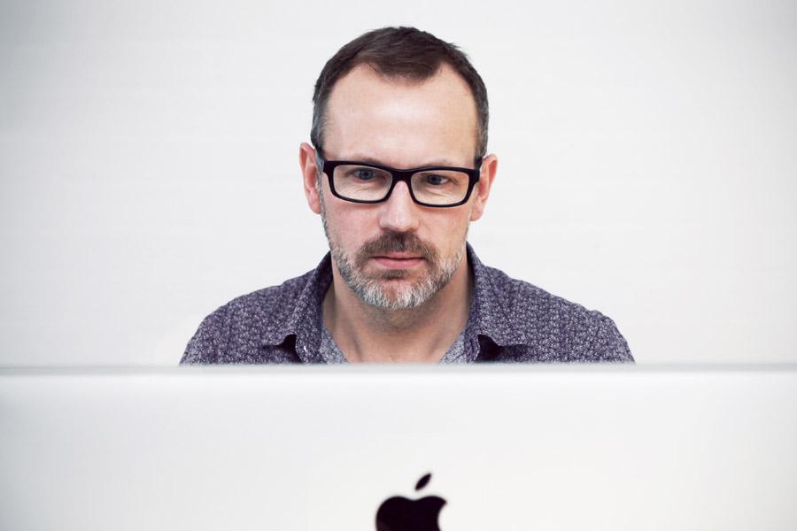 フリー写真 パソコンのモニタと仕事中の中年男性
